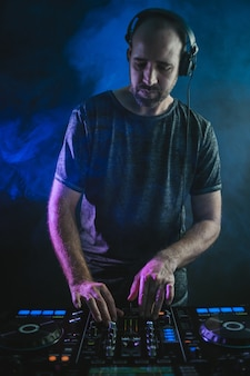Vertikales bild eines männlichen dj unter den blauen lichtern und dem rauch