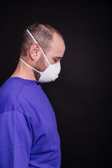 Vertikales bild eines mannes mit einer gesichtsmaske vor einem dunklen hintergrund - covid-19