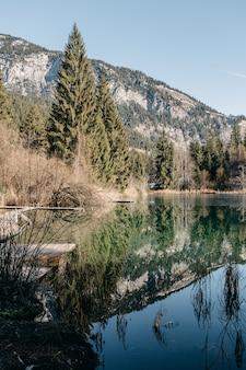 Vertikales bild eines sees, umgeben von felsen und wäldern mit bäumen, die auf dem wasser reflektieren