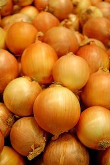 Vertikales bild eines stapels der zwiebeln, die am markt verkaufen