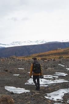 Vertikales bild eines wanderers mit einer kamera auf den im schnee bedeckten hügeln in island