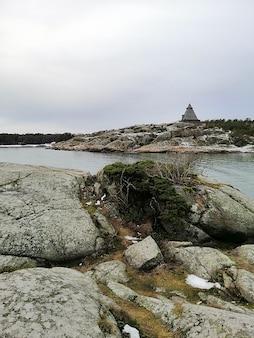 Vertikales bild von felsen, die durch den fluss unter einem bewölkten himmel in norwegen umgeben sind