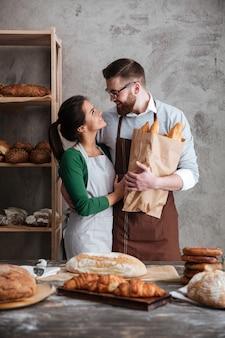 Vertikales bild von glücklichen bäckern in der bäckerei