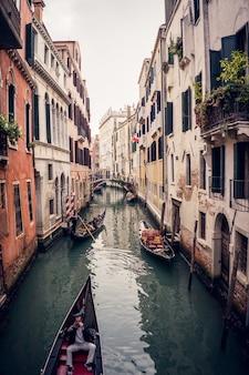 Vertikales bild von gondeln auf dem großen kanal zwischen bunten gebäuden in venedig, italien