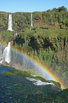 Vertikales bild von starkem iguazu falls an der brasilianischen seite mit einem enormen regenbogen, foz tun iguacu, brasilien