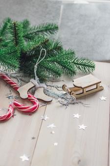 Vertikales bild von zuckerstangen und weihnachtsdekorationen auf einem holztisch unter den lichtern