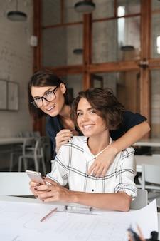 Vertikales bild von zwei jungen glücklichen frauen, die smartphone verwenden