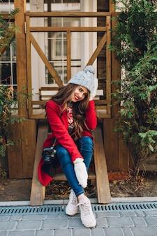 Vertikales brünettes mädchen in voller länge mit langen haaren im roten mantel und gestrickter mütze, die auf holztreppen im freien sitzt. sie trägt warmweiße handschuhe und lächelt.