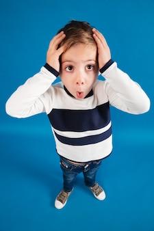 Vertikales draufsichtbild des schockierten jungen im pullover