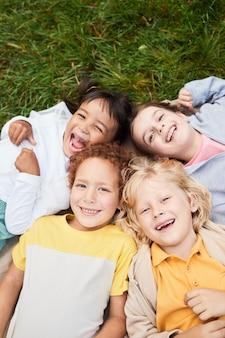Vertikales draufsichtporträt einer verschiedenen gruppe von kindern, die auf gras im park liegen und kameras...
