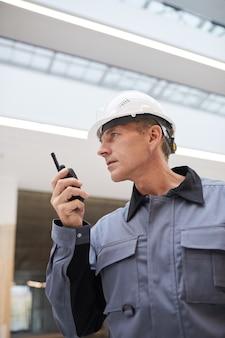 Vertikales flachwinkelporträt eines reifen arbeiters, der durch walkie-talkie spricht, während arbeit auf der baustelle oder in der industriewerkstatt überwacht wird,