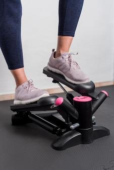 Vertikales foto der fitnessfrau, die stepper zu hause verwendet.
