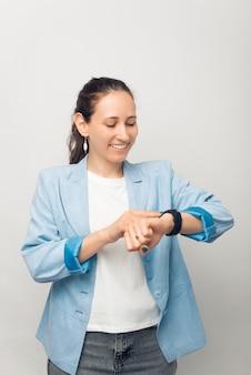 Vertikales foto der jungen frau in freizeitkleidung mit smartwatch auf weißem hintergrund