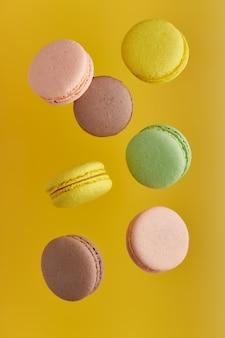 Vertikales foto der makrone. bunter kuchen macaron mit pastelltönen in chaotischer levitation auf gelber oberfläche draufsicht auf mandelkekse.