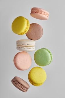 Vertikales foto der makrone. bunter kuchen macaron mit pastelltönen in chaotischer levitation auf grauer wand. draufsicht auf mandelkekse.