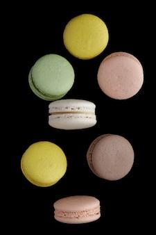 Vertikales foto der makrone. bunter kuchen macaron mit pastelltönen in chaotischer levitation auf schwarzer wand. draufsicht auf mandelkekse.