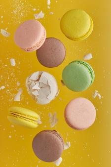Vertikales foto der makrone. bunter kuchen macaron mit pastelltönen und weißer rissiger makrone mit krümeln in chaotischer levitation auf einer gelben wand. draufsicht auf mandelkekse.