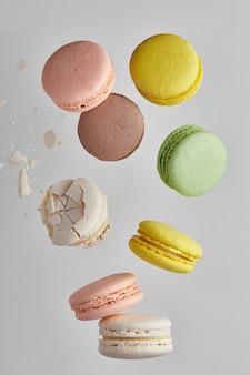 Vertikales foto der makrone. bunter kuchen macaron mit pastelltönen und weißer rissiger makrone mit krümeln in chaotischer levitation fallen auf den stapel auf grauer wand. draufsicht auf mandelkekse.