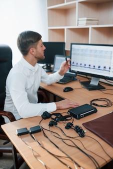 Vertikales foto. der polygraph-prüfer arbeitet im büro mit der ausrüstung seines lügendetektors