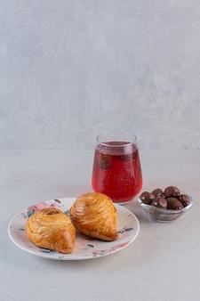 Vertikales foto des frischen croissants mit saft und schokolade