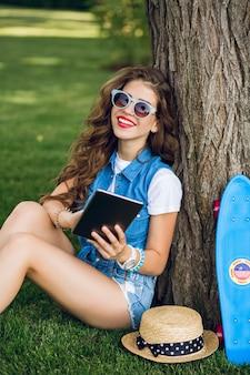 Vertikales foto des hübschen mädchens mit dem langen lockigen haar in der sonnenbrille, die nahe baum im sommerpark sitzt. sie trägt jeansshorts, wams und turnschuhe. sie hält das tablet in der hand und lächelt in die kamera.