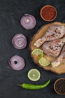 Vertikales foto des marinierten hühnertrommelstocks und des gemüses.