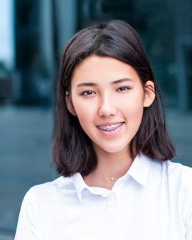 Vertikales foto des schönen jungen asiatischen mädchens, des teenagers, des studenten. chinesische, japanische oder koreanische frau, die in klammern lächelt, die kamera betrachten. porträt der attraktiven hübschen glücklichen dame, jugendlich. gesunde zähne