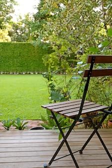 Vertikales foto des vibrierenden rasenhinterhofs des grünen grases mit einem holzstuhl für die entspannung