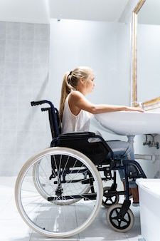 Vertikales foto einer blonden frau, die in einem rollstuhl in einem badezimmer sitzt
