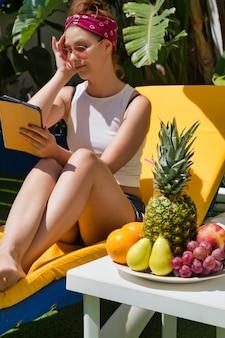 Vertikales foto einer frau, die einen turban und eine sonnenbrille auf einer sonnenbank trägt, die ihr haar berührt, während sie eine tablette mit einem obsttisch verwendet