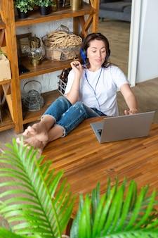Vertikales foto einer glücklich lächelnden frau mit blauen kopfhörern vor einem laptop-monitor zu hause, die sie ...
