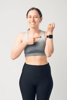 Vertikales foto einer jungen frau, die auf ihre smartwatch am handgelenk zeigt, während sie sportkleidung trägt.