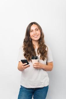 Vertikales foto einer jungen frau, die ihr telefon und eine tasse kaffee zum mitnehmen hält.