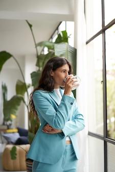 Vertikales foto einer jungen geschäftsfrau, die ihren morgenkaffee oder -tee genießt und aus dem fenster schaut