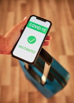 Vertikales foto einer touristenhand, die covid-19-impfbescheinigung auf smartphone mit reisekoffer zeigt