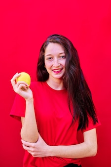 Vertikales foto eines jungen brünetten mädchens, das in die kamera schaut, die einen gelben apfel auf rotem hintergrund hält