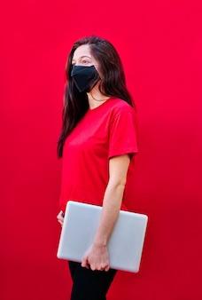Vertikales foto eines jungen brünetten studentenmädchens mit maske, das einen laptop auf flachem rotem hintergrund trägt