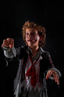 Vertikales foto eines kindes, das als zombie mit blut und glitzer verkleidet ist, mit erhobenen armen zu fuß. halloween