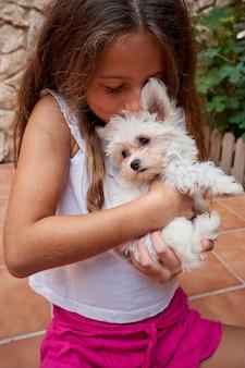Vertikales foto eines mädchens, das einen kleinen weißen hund küsst, der in ihren armen gehalten wird. haustiere und familie