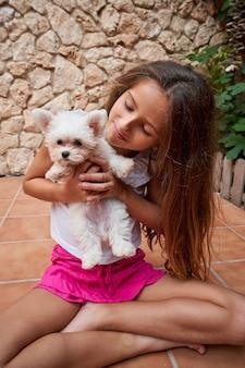 Vertikales foto eines mädchens, das sitzt und einen kleinen weißen hund betrachtet, den sie in ihren armen hat. haustiere und familie