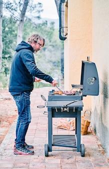 Vertikales foto eines mannes mittleren alters, der fleisch auf dem grill im hinterhof des hauses kocht