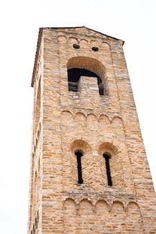 Vertikales foto eines mittelalterlichen steinturms mit bögen an der fassade. villefranche de conflent in frankreich