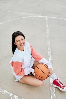 Vertikales foto eines schönen jungen mädchens, das basketball spielt blick in die kamera platz kopieren