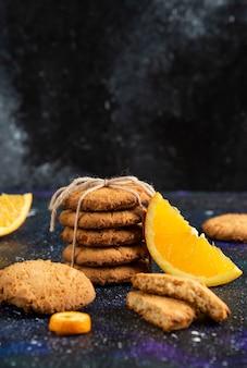 Vertikales foto eines stapels hausgemachter kekse mit orangenscheibe über der weltraumoberfläche
