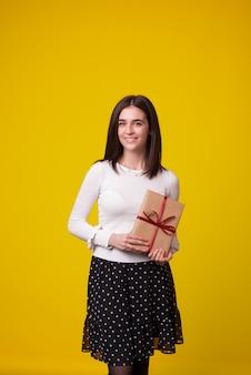 Vertikales foto eines stehenden mädchens, das ein geschenk in seinen händen präsentiert.