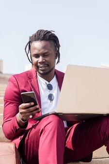 Vertikales foto eines stilvollen afrikanischen geschäftsmannes, der im freien mit laptop und smartphone arbeitet