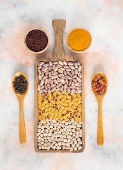 Vertikales foto. haufen von getreideprodukten auf holzbrett. bean, pasta und kichererbse mit gewürzen.