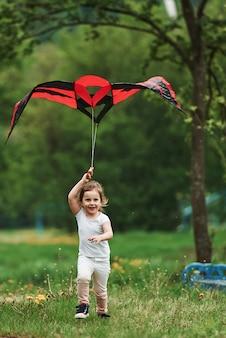 Vertikales foto. positives weibliches kind, das mit rotem und schwarzem drachen in den händen draußen läuft