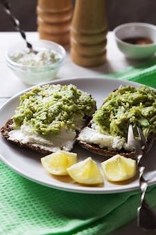 Vertikales foto von avocadosandwichen mit hüttenkäse- und zitronenscheiben