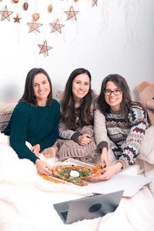 Vertikales foto von drei freundinnen, die die kamera betrachten, während sie jeweils ein stück pizza nehmen.